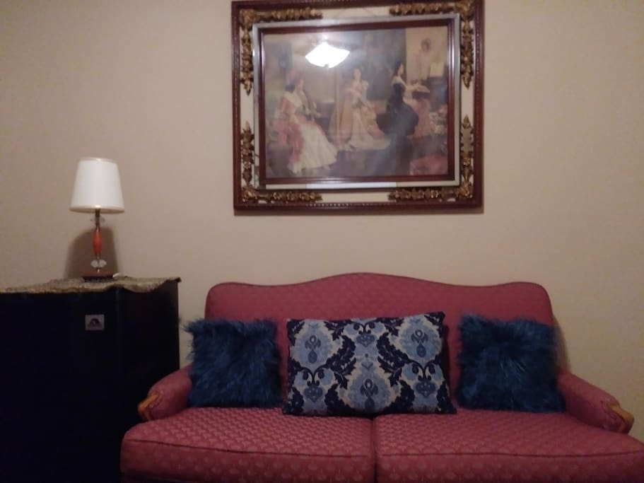 Period couch, lamp, wall art; plus your own minifridge.