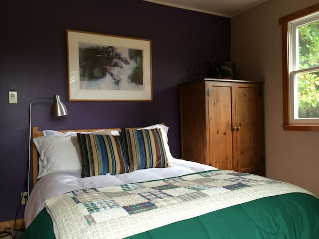 Bedroom on the upper level of the house with a double bed and amazing views and deck access to the top deck.