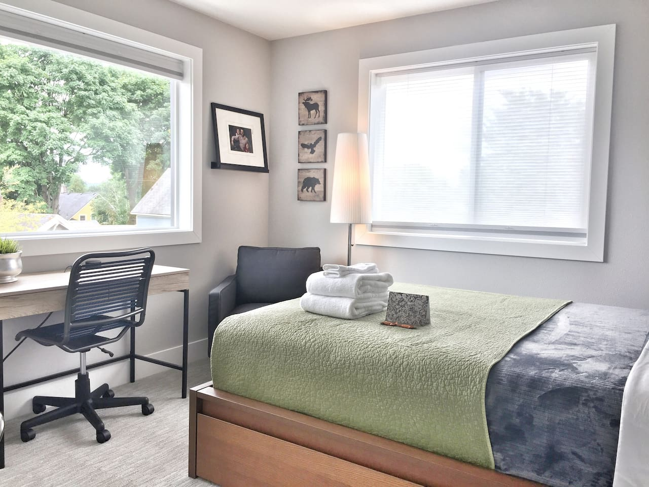 This room features a queen size memory phone bed, linens, lamp, side chair, alarm clock, desk, chair, and large windows with room darkening shades.