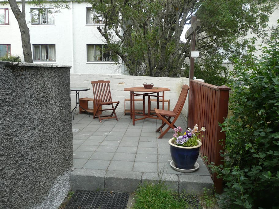 Going past the stairs is a lovely garden terrace with furniture and a grill