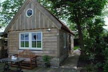 Dit is de cottage gezien vanaf de sloot met gezellig zitje waar ook gegeten kan worden.
