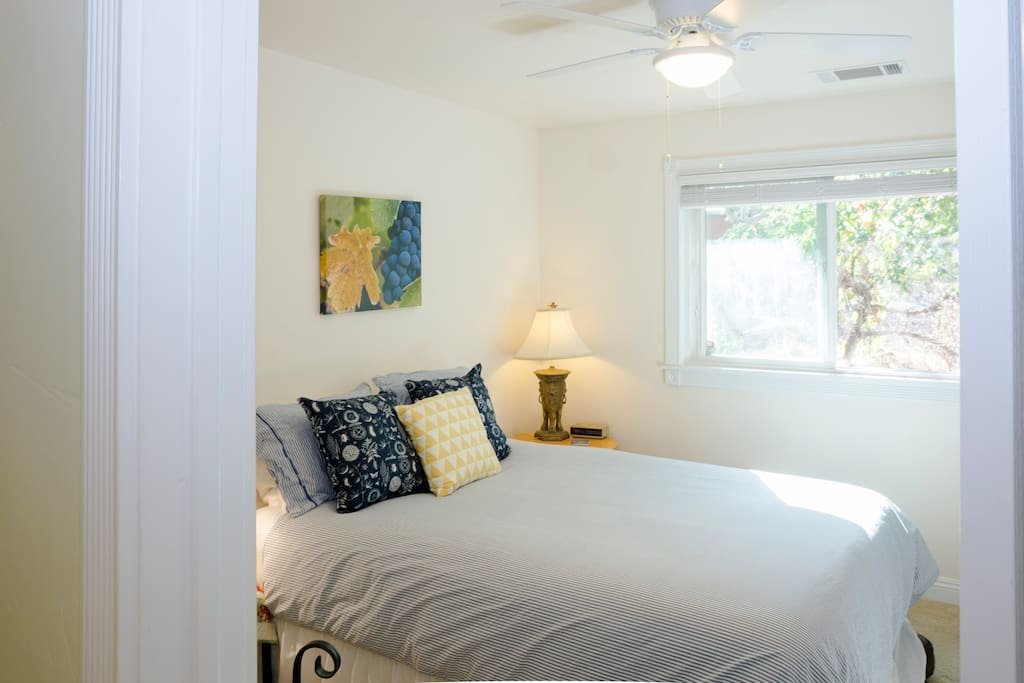 Comfortable queen sized bed with ceiling fan, window and large closet.