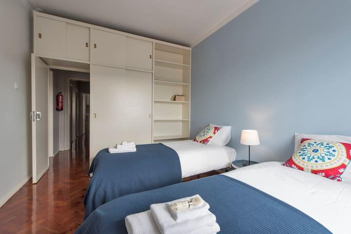 Bedroom with two single beds, labtop desk and wardrobe. Quarto com duas camas individuais, secretária para portátil e guarda-roupa.
