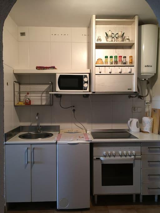 la cocina tiene horno, microhonda y lavadora con apertura de carga superior