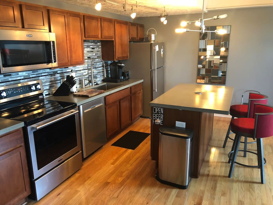 Kitchen has been completely updated with custom concrete counters and high end stainless steel appliances.