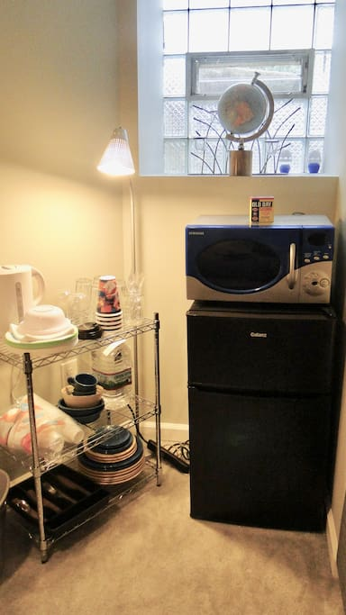 Kitchenette nook with mini-fridge, microwave, electric kettle, plates, and utensils