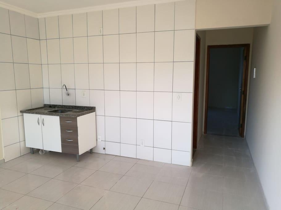 Cozinha/Sala, acesso ao quarto. Para a estadia ainda contará com um frigobar, um armário e mesa para 2 lugares.