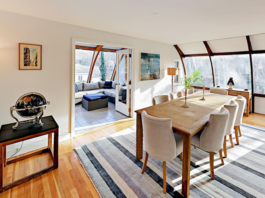 The bright dining room is just beyond the kitchen and has a large table with 8 cushioned chairs and huge windows overlooking the backyard.