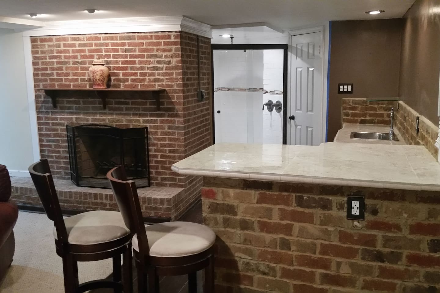 Fireplace, bar, cooktop stove and under bar refrigerator