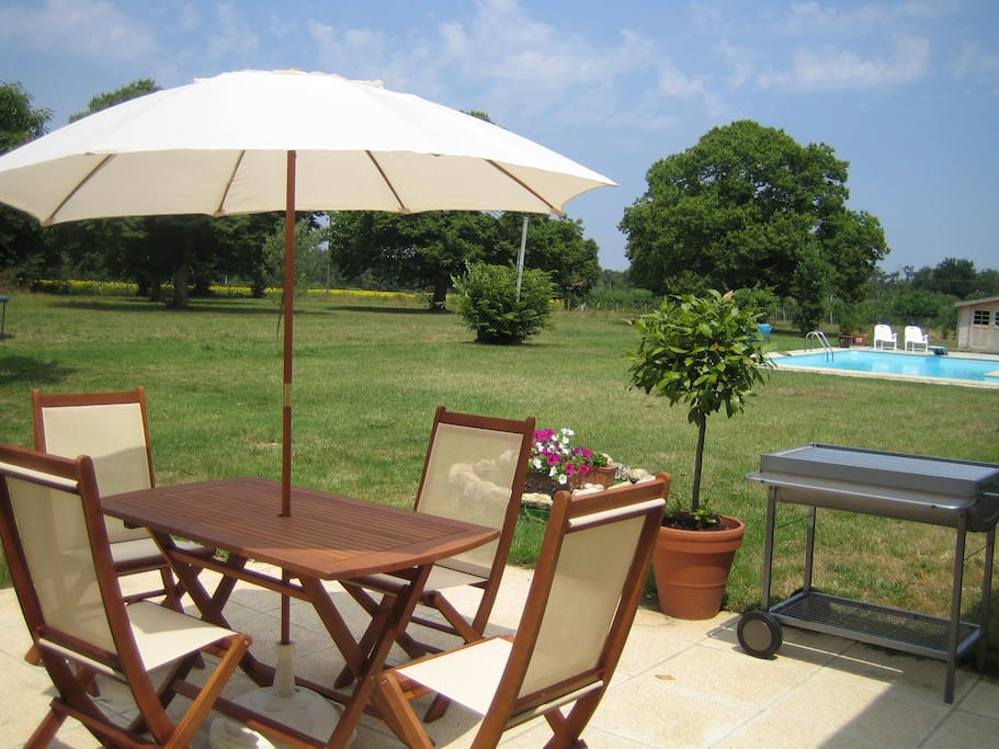 The gite - patio overlooking the pool with charcoal bbq.