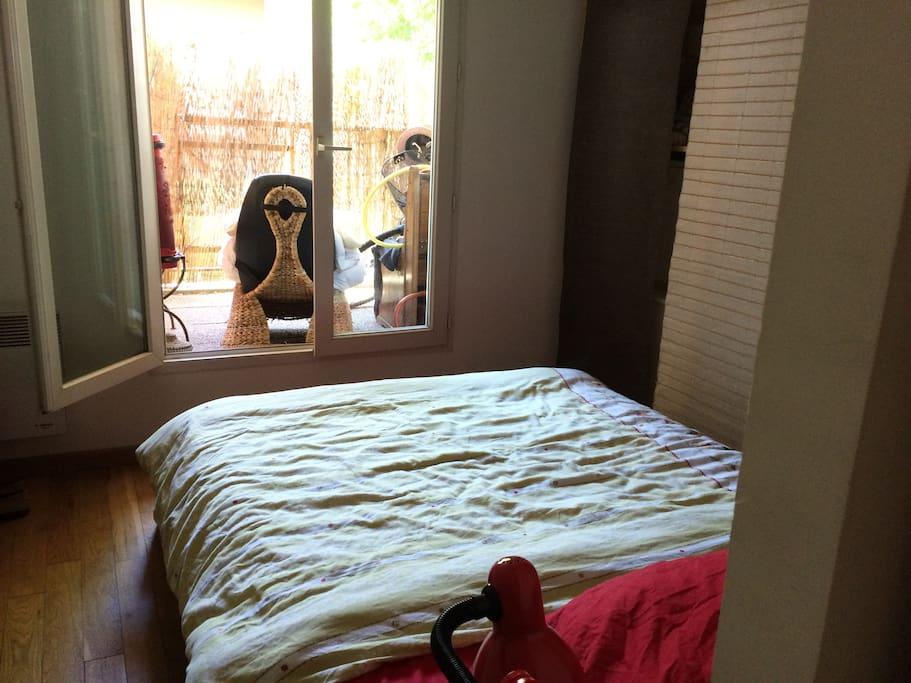 La chambre avec le lit double et des rangements pour les vêtements