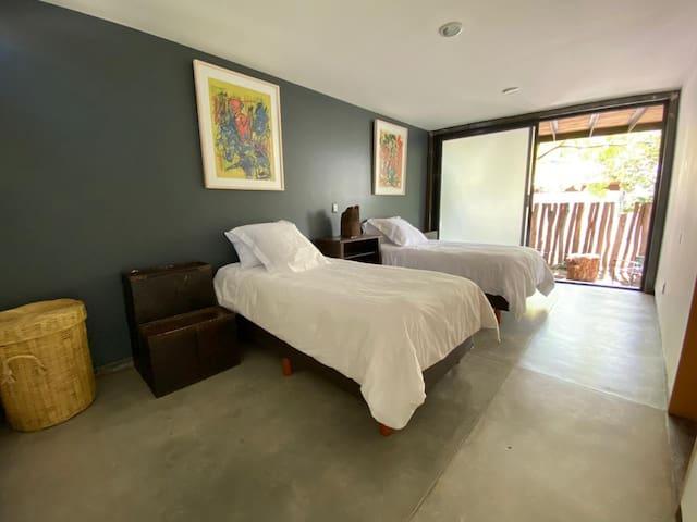 Habitación con dos camas individuales, baño propio y terraza exterior
