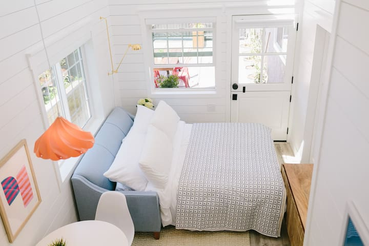 """We had a custom couch built to fit our #tinyhome.  The mattress is a Queen that's a full 5"""" thick.  (It's not the regular sofa mattress that's uncomfortable & thin).  We additionally have a roll-out twin and pack n' play available upon request."""