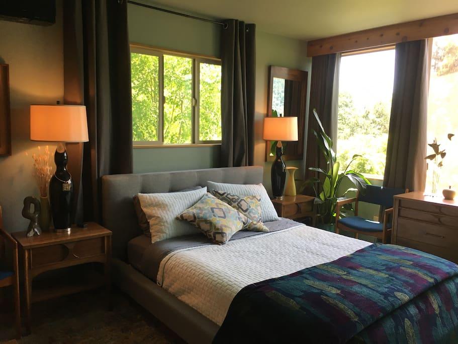 Comfortable queen bed in master bedroom with bank of windows overlooking the view.