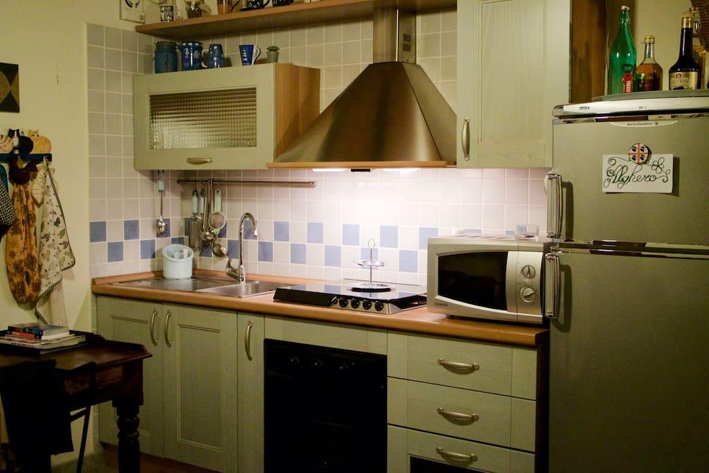 Angolo cottura con forno statico, forno a microonde, cappa e ventola.