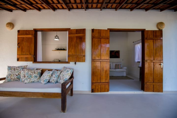 Entrada do bangalô, na área externa possui varanda com rede e/ou sofá, e/ou mesa com cadeiras.