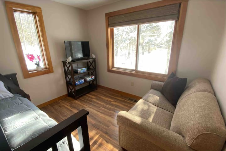 """Bunk Bedroom on Main Level (twin-over-full) with 32"""" Roku SmartTV and new (2021) pullout twin sleeper sofa."""