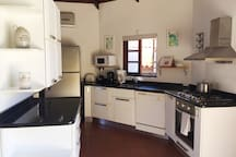 Kitchen with dishwasher, oven, 4-pits cooktop, large fridge and microwave.