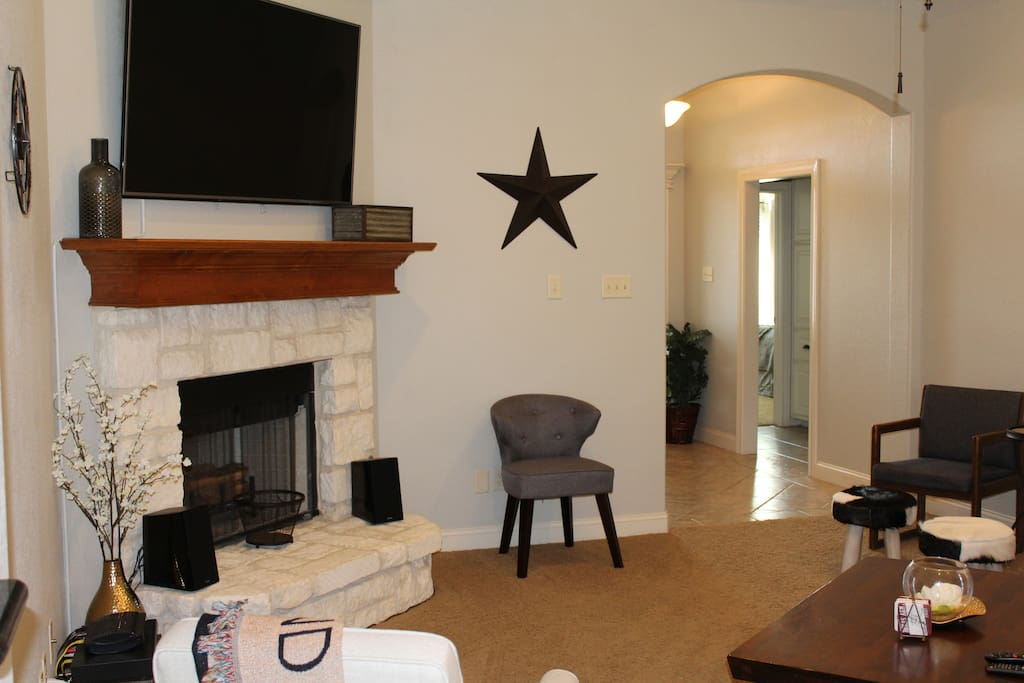 65'' TV in living room with plenty of seating. Recliner, 3 chairs, and large sofa.