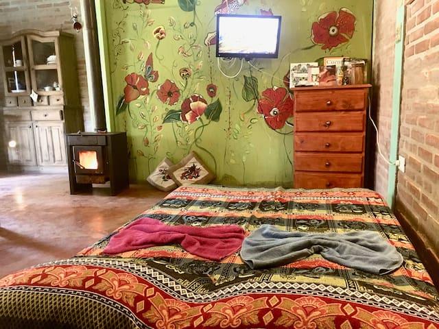 Habitación principal tipo loft con salamandra a leña, tv, wifi, doble entrada, paredes con murales artísticos muy bellos.