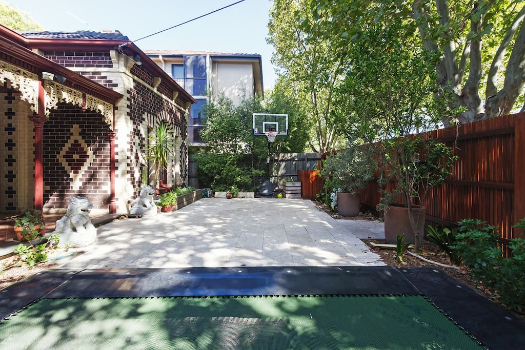 Travertine courtyard with trampoline and basketball hoop on leafy street