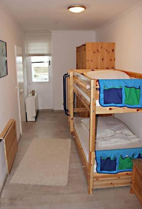 Das Kinderzimmer. Im stabilen Hochbett können natürlich auch Erwachsene schlafen. Ein neues Kinderreisebettchen steht - falls benötigt - auch parat.