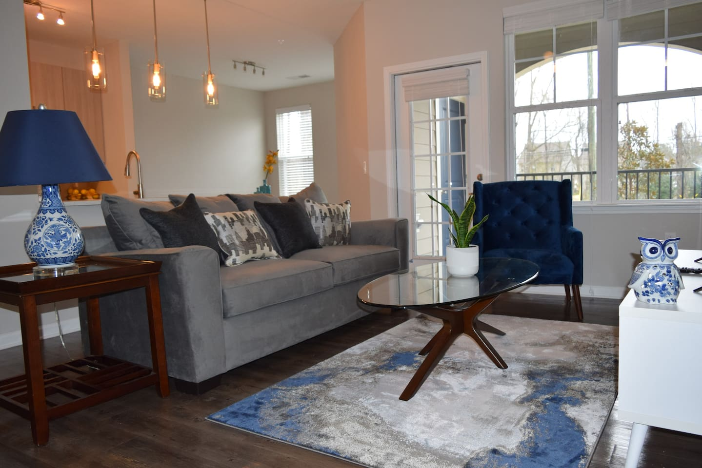 Living room with 43' 4k Roku TV, large glass coffee table, comfortable couch, and accent chair.
