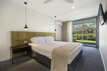 Master Bedroom with glass sliding doors opening to manicured lawn and Noosa River views