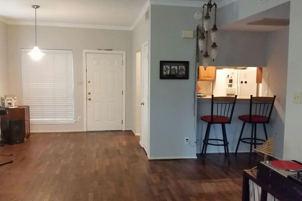 View of front door with kitchen and bar top on the right.
