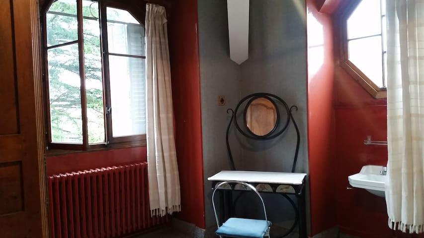 Chambre à coucher avec 2 fenêtres, une donnant vue sur parc arboré et la 2è exagonale donnant sur la rue privée, lavabo, table de maquillage, armoire de rangements.