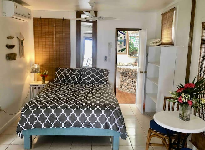 Your queen bed, sitting area, and bathroom
