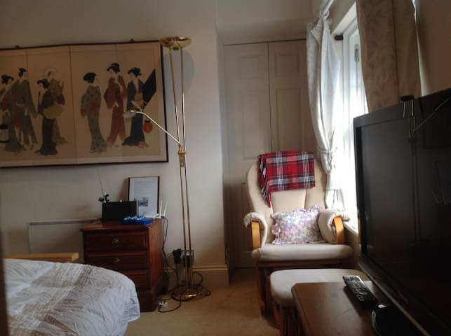 Rocking chair by main window in bed-sitting room