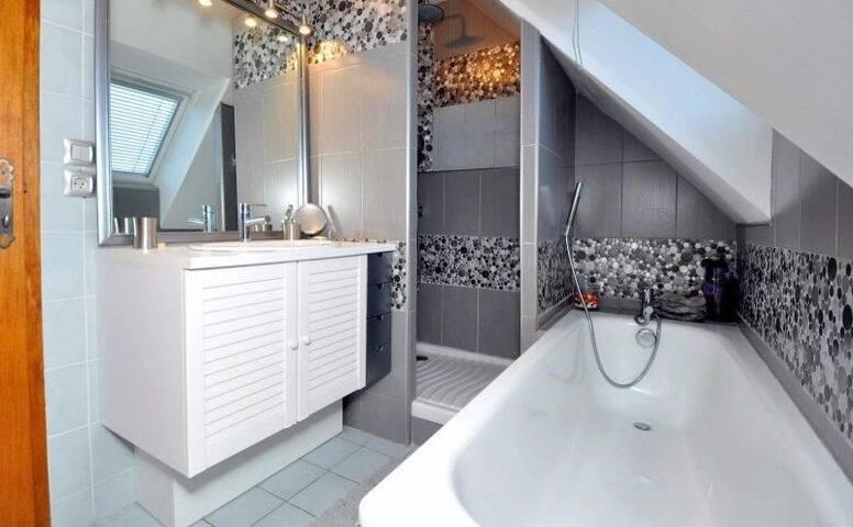 Première salle de bain équipée de douche et baignoire.  Un sèche cheveux est à votre disposition. Étant donné la configuration de la maison, cette salle de bain peut être exclusive pour une chambre double.