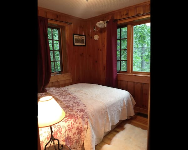 Bedroom with full size bed. With the windows open, fall asleep to the tranquil soundtrack of the waterfall below.