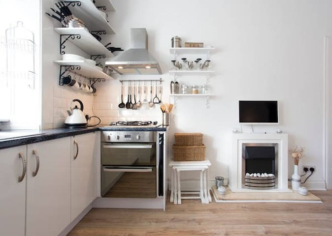 Kitchen leading on to living room with electric fire place for extra cosy-ness.