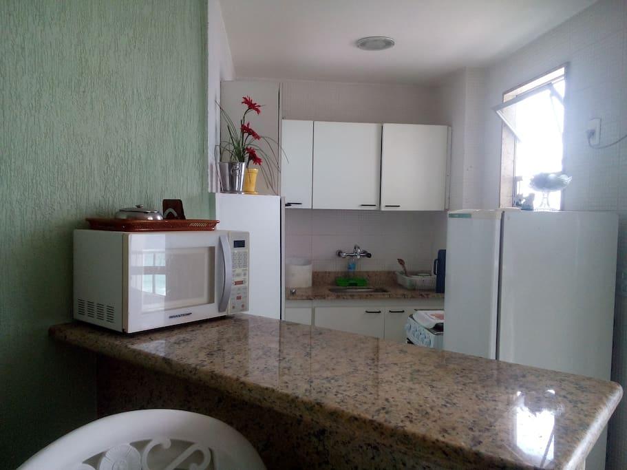 Vista da cozinha com seus armários, micro ondas, geladeira e fogão