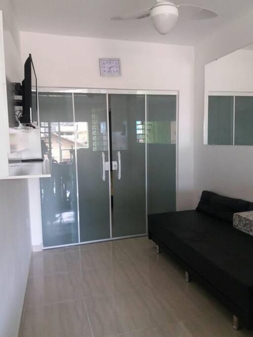 Sala com sofá cama, cama extra, ventilador de teto e tv