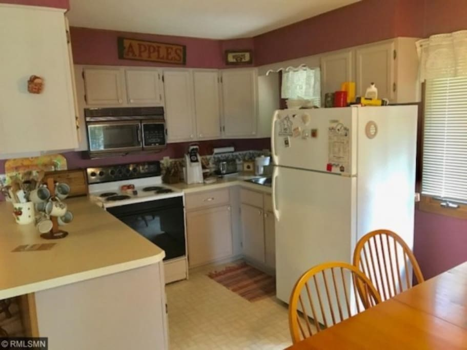 Kitchen area includes electric stove, oven, and microwave with fridge and freezer