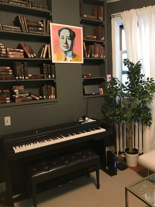 The living room features a piano, a library of vintage books and a Bose sound dock that is compatible with all iPhones.