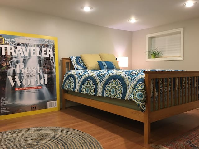 A queen size bed awaits with downy comforter and extra pillows.  There is recessed lighting throughout the space.