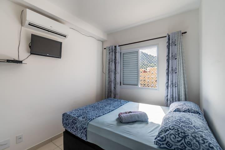 Quarto de casal com ar condicionado, TV, armários.
