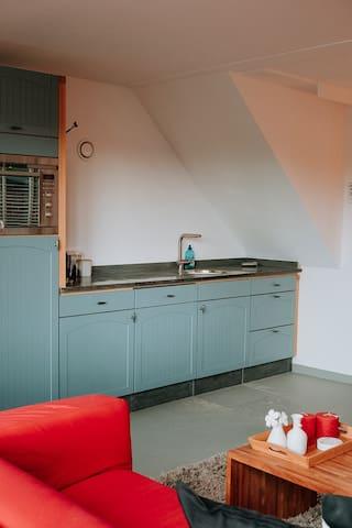 keuken gezien vanuit zithoek voorzien van vaatwasser, kookplaat, koelkast, oven en magnetron