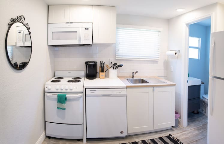 Spotless kitchen with stove, microwave, dishwasher and Keurig coffee maker. Stocked with silverware, plates, pots, pans and cutlery.