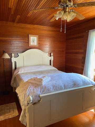 Queen bed, wood floor, wood bead-board on walls and ceiling.