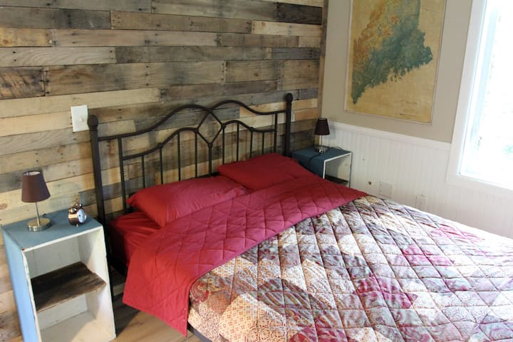 Queen sized bed. Barn wood accent wall with vintage map of Maine. Repurposed antique dovetail boxes as nightstands.