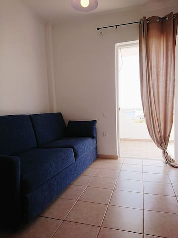 Bedroom with window door and private balcony with sea view.  The midnight-blue sofa can turn into a comfortable bed. On the corner there is also a desk and a bookcase, making this room ideal for study or work purposes.
