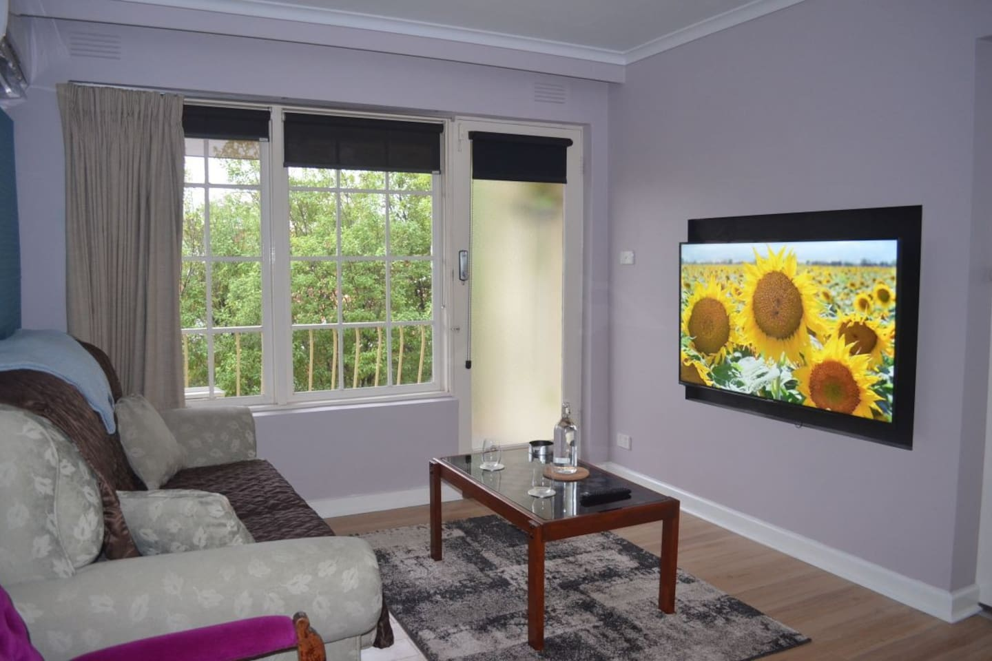 loungeroom with games table, smart tv and balcony.