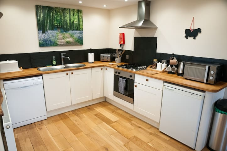 Modern kitchen with gas hob, solid beech worktop, dishwasher, microwave & toaster