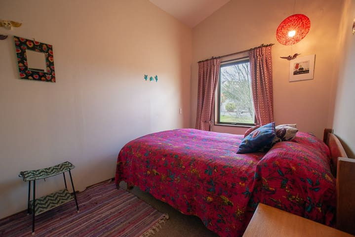 """The """"Frida Carlo Room"""" with slat double bed and a view onto the garden and quiet street."""