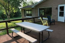 Large deck with chairs, picnic table, and charcoal grill for your backyard BBQ.